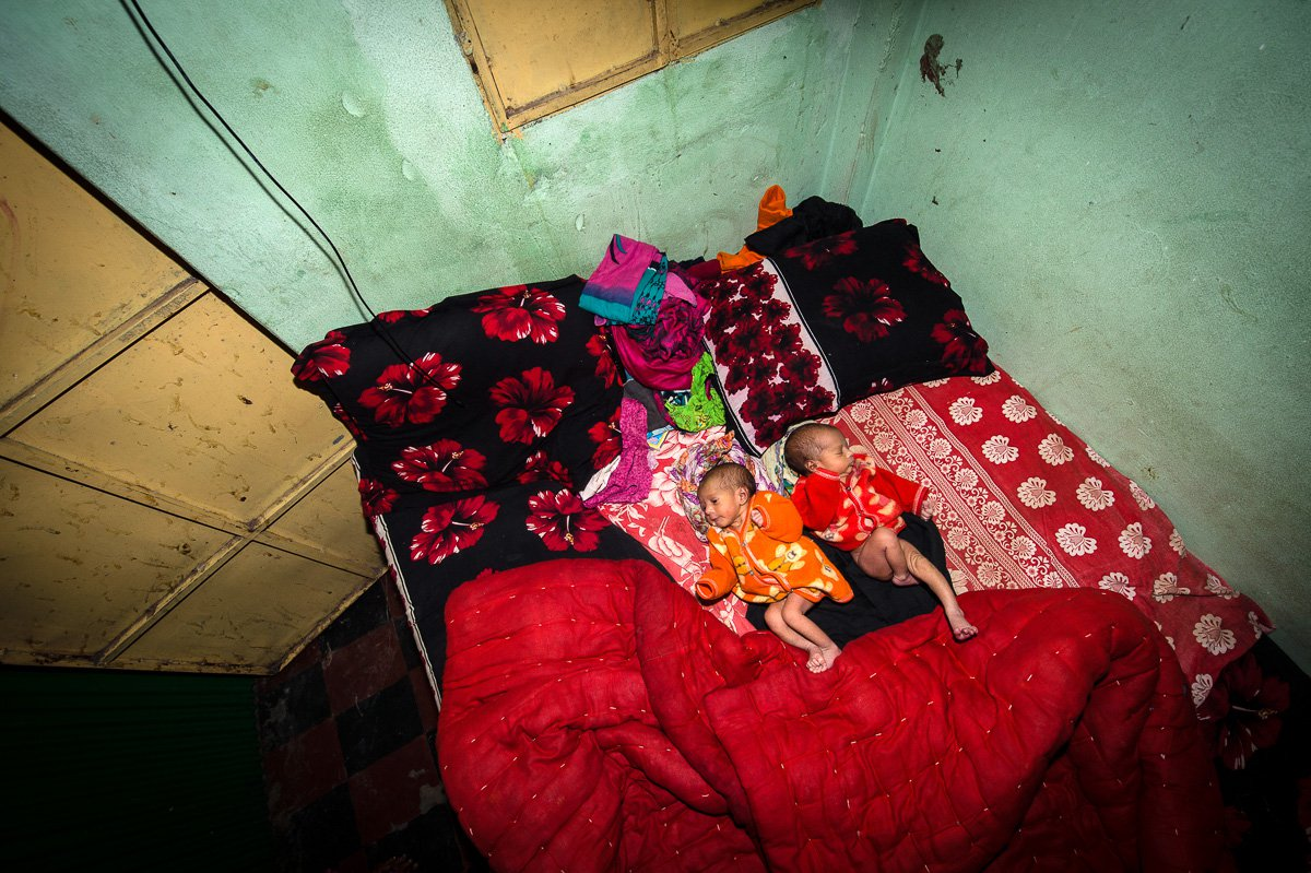 Five days old twins lie on the bed. They have not yet a name. Jhinik, 20 years, a sex worker in the Kandapara brothel gave birth to them.