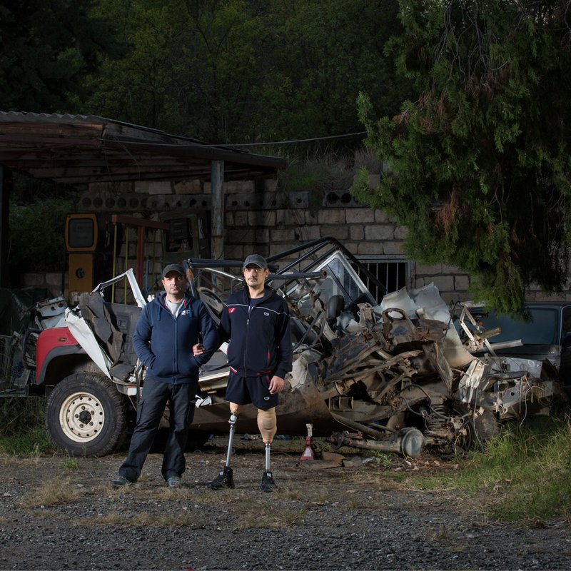 Two sappers stand near the blown-up car exploded in 2018. On the way to the demining site, there were five people in the car. Three out five died instantly, the other two survived, and keep working as sappers.