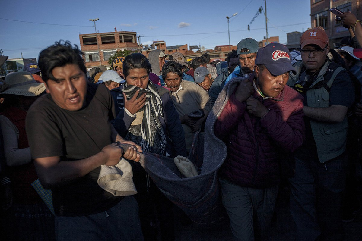 Supporters of Bolivian ex-President Evo Morales move the body of their comrade to the local chapel. 