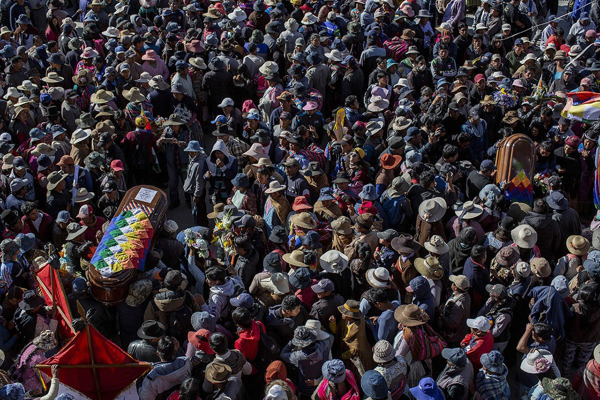 Mourners carry the coffin with remains of a man to the San Francisco de Asis church during the other six people's funeral. 