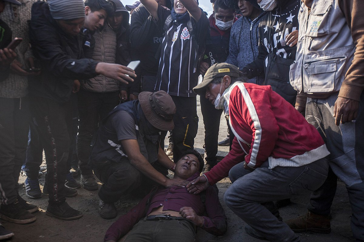 Comrades help a supporter of Bolivian ex-President Evo Morales after he got shot during clashes with security forces. 