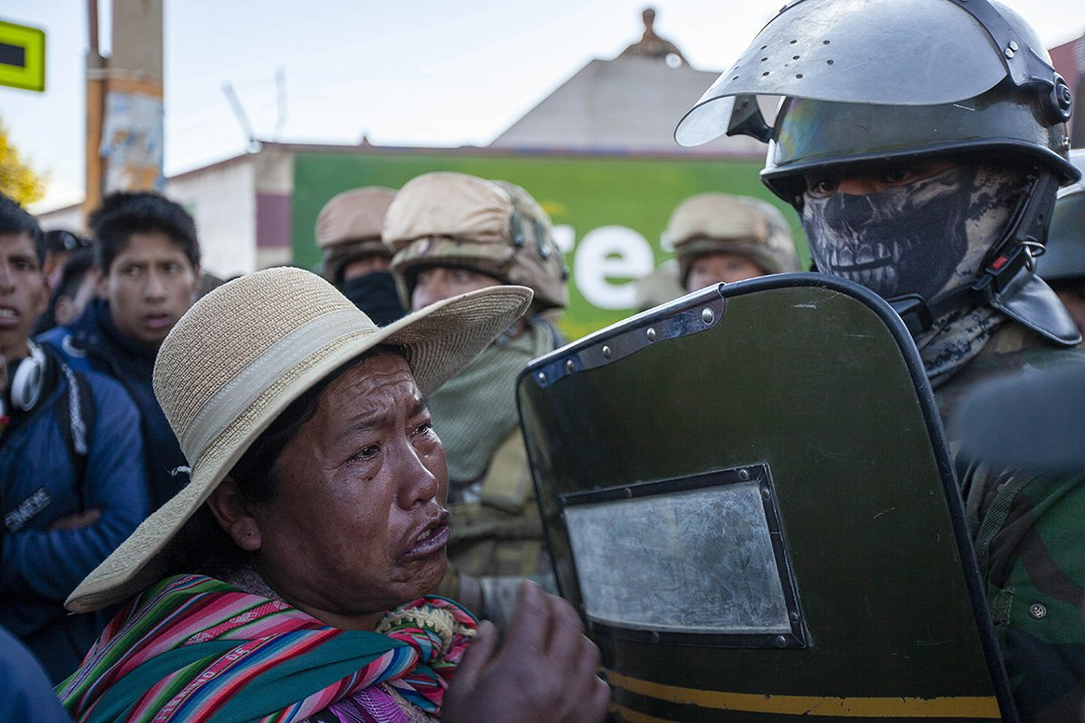 An indigenous woman cries as she faces a soldier guarding the Senkata field plant, after clashes in El Alto on the outskirts of La Paz, Bolivia. On Tuesday, security forces escorted gasoline tankers from the plant, which had been blockaded for five days by supporters of former Bolivian President Evo Morales, and at least nine people were killed during clashes that followed the operation.
